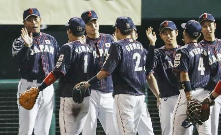 カナダに勝利し、山田哲(1)らを迎える稲葉監督(左端)=沖縄セルラー