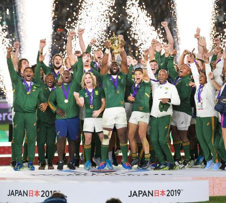 ラグビーW杯日本大会で優勝し、ウェブ・エリス・カップを掲げ喜ぶコリシ主将(中央)と南アフリカフィフティーン=2日夜、横浜市の日産スタジアム