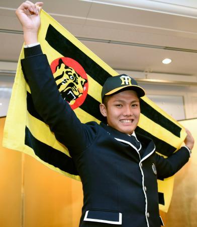 阪神への入団が決まり、笑顔でポーズをとるドラフト1位の西純矢投手=4日、岡山市