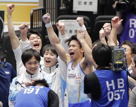 男子団体で初優勝し、喜ぶ萱和磨(中央)らセントラルスポーツの選手たち=高崎アリーナ