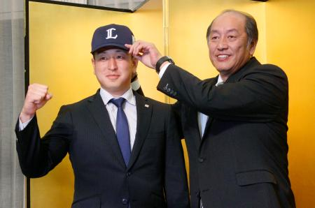 西武入団に合意し、渡辺久信GMから帽子をかぶせてもらうドラフト1位の宮川哲投手=12日、東京都内