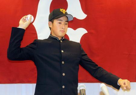 記者会見でポーズをとる、巨人入団が決まった青森山田高の堀田賢慎投手=13日、青森市