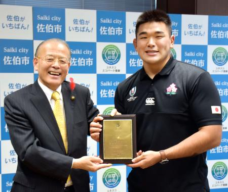大分県佐伯市の田中利明市長(左)から市長賞詞を授与された、ラグビーW杯日本代表の具智元選手=14日午後、佐伯市役所
