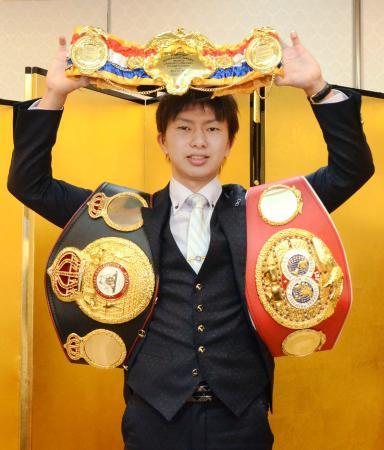記者会見でチャンピオンベルトを掲げるライトフライ級の元統一王者田口良一=20日、東京都内