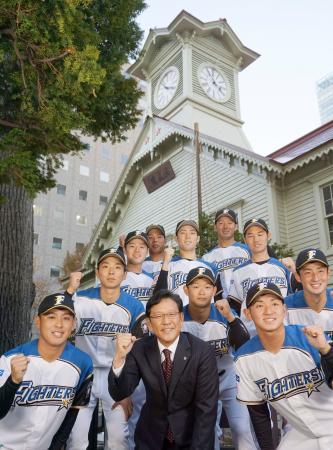 時計台の前でポーズを取る日本ハムの栗山監督(前列中央)とドラフト1位の河野竜生投手(同左)ら新入団選手=23日、札幌市