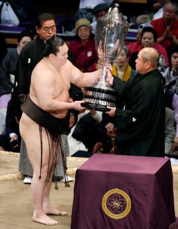 大相撲九州場所で43度目の優勝を果たし、日本相撲協会の八角理事長(右)から賜杯を受け取る白鵬=24日、福岡国際センター
