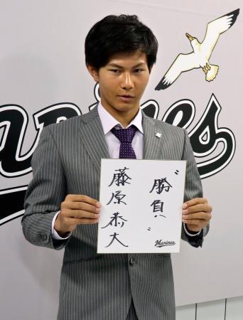契約更改を終え、記者会見で色紙を手に写真撮影に応じるロッテの藤原恭大外野手=27日、千葉市のZOZOマリンスタジアム