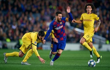 サッカーの欧州チャンピオンズリーグ1次リーグ第5戦F組で、ドルトムント(ドイツ)の選手と競り合う、バルセロナ(スペイン)のメッシ(中央)。(ゲッティ=共同)