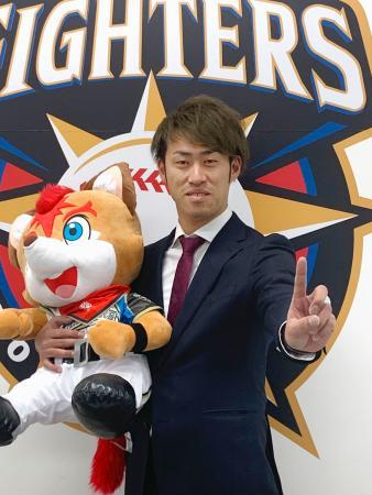 年俸1億円の大台に復帰し、「1」のポーズをとる日本ハムの秋吉亮投手=28日、札幌市