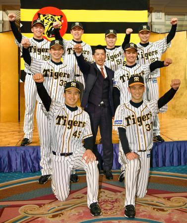 阪神の入団記者会見でポーズをとる(左上から時計回りに)奥山皓太外野手、小川一平投手、藤田健斗捕手、小野寺暖外野手、西純矢投手、及川雅貴投手、遠藤成内野手、井上広大外野手。中央は矢野監督=2日、大阪市内のホテル
