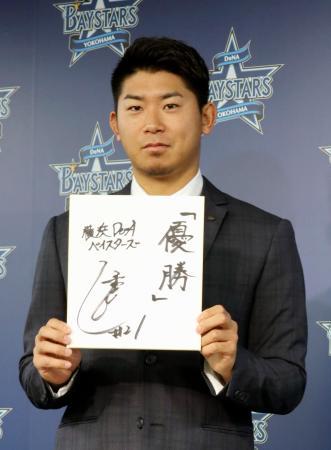 契約更改後に記者会見で、来期の抱負を記した色紙を手にポーズをとるDeNAの今永=5日、横浜市の球団事務所