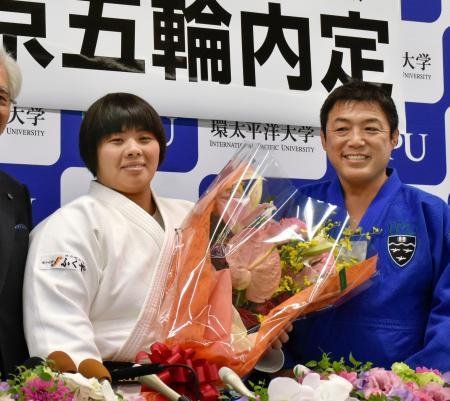 岡山市の環太平洋大で花束を贈られ笑顔の素根輝。右は総監督を務める古賀稔彦氏=9日