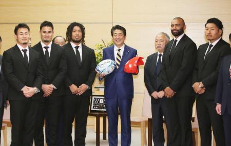 安倍首相(中央)と面会し、記念のラグビーボールとTシャツを贈ったラグビーW杯日本代表のリーチ・マイケル選手(右から2人目)ら=11日午後、首相官邸