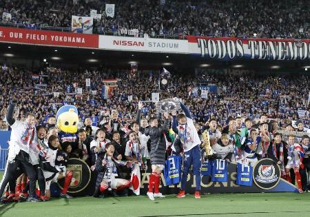 15年ぶり4度目の優勝を果たし、スタンドのサポーターと喜ぶ横浜Mイレブン=日産スタジアム