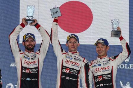 WECシリーズ第4戦で優勝を果たし、表彰台でトロフィーを掲げるトヨタ7号車の小林可夢偉(右)ら=14日、サキール(ゲッティ=共同)