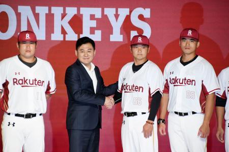 台湾球団「楽天モンキーズ」のユニフォームを披露する選手と楽天の三木谷浩史会長兼社長(左から2人目)=17日、台北(共同)