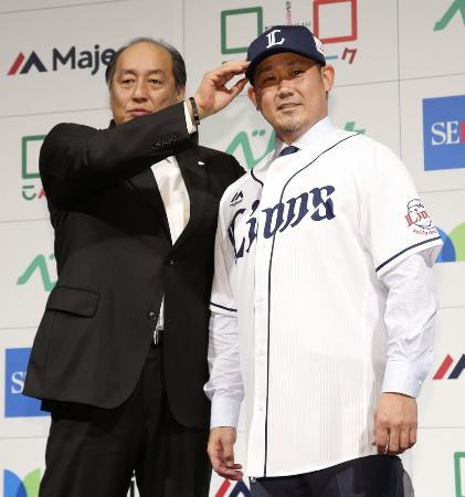 西武の入団会見終了後、渡辺GM(左)に帽子をかぶせてもらう松坂大輔投手=12月11日、東京都内のホテル