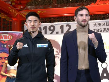 ボクシング世界戦の調印式でポーズをとるWBOスーパーフライ級王者の井岡一翔(左)と挑戦者のジェイビエール・シントロン=25日、羽田空港