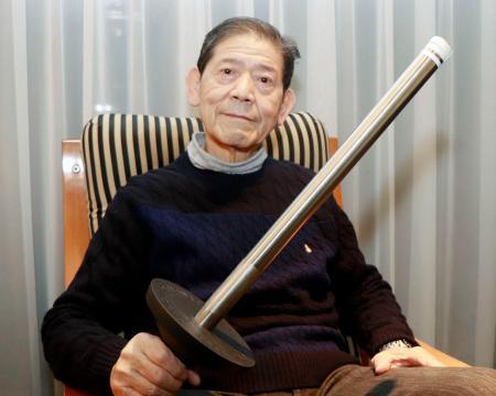 1964年東京五輪の聖火リレーで使ったトーチのホルダーを手にする村上健さん=神戸市
