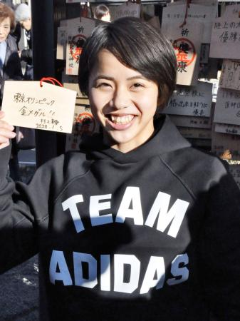 東京五輪での目標を書いた絵馬を片手に笑顔を見せる村上茉愛=5日、川崎市
