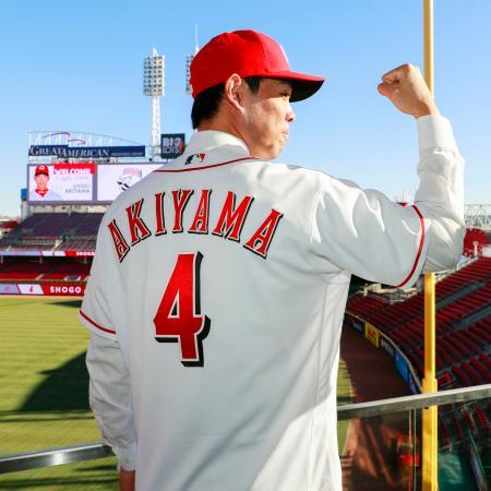 米大リーグ、レッズの入団会見後、球場を背にポーズを決める秋山翔吾外野手=8日、シンシナティ(共同)