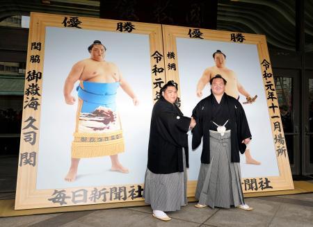 優勝額贈呈式で握手を交わす御嶽海(左)と白鵬=11日、両国国技館