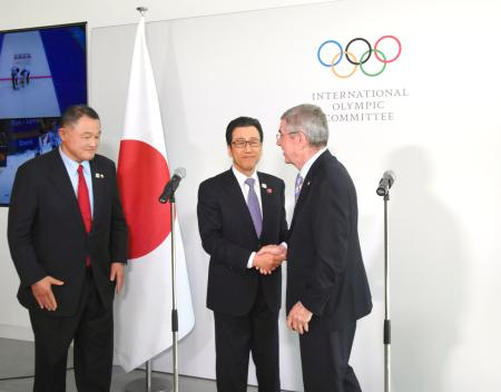 会談後、バッハIOC会長(右)と握手を交わす秋元克広・札幌市長。左は山下泰裕JOC会長=11日、ローザンヌ(共同)