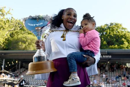長女オリンピアちゃんを抱き、優勝トロフィーを手に笑顔を見せるセリーナ・ウィリアムズ=12日、オークランド(ゲッティ=共同)