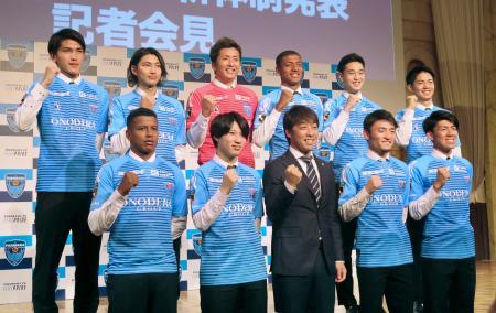 新体制発表の記者会見で、ポーズをとる横浜FCの下平監督(前列中央)ら=13日、横浜市内