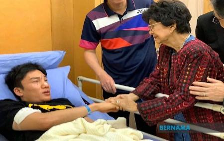 事故で顔を負傷し、病院でマレーシア首相夫人から見舞いを受ける桃田賢斗選手(左)=13日、クアラルンプール近郊プトラジャヤ(ベルナマ通信提供・共同)