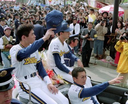 1995年、オリックスがリーグ優勝し、「がんばろうKOBE」のロゴが入ったユニホームで優勝パレードするイチロー(左)ら。右下は仰木監督=神戸市