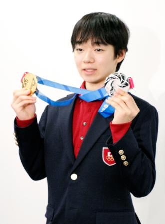 冬季ユース五輪を終えて帰国し、メダルを掲げるフィギュアスケート男子の鍵山優真=17日、羽田空港