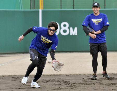 ノックを受けるソフトボール女子日本代表の上野。右はプロ野球巨人の菅野=福岡県久留米市
