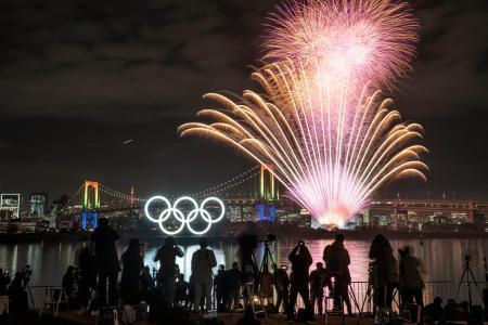 東京五輪の開幕まで半年となり、お台場海浜公園の水上に設置された五輪マークのモニュメントがライトアップされ、記念の花火が祭典ムードを盛り上げた=24日夜、東京・お台場