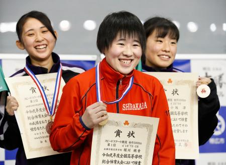 スピード女子3000メートルの表彰式で笑顔を見せる、大会新記録で優勝した白樺学園・堀川桃香(中央)=明治北海道十勝オーバル