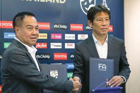 タイ・サッカー協会と契約を延長した、同国代表の西野朗監督(右)=24日、バンコク(共同)