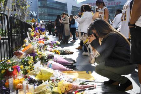 27日、米プロバスケットボールNBAレーカーズの本拠地ステープルズセンターの前で、コービー・ブライアント氏の死を悼むファンら=ロサンゼルス(共同)