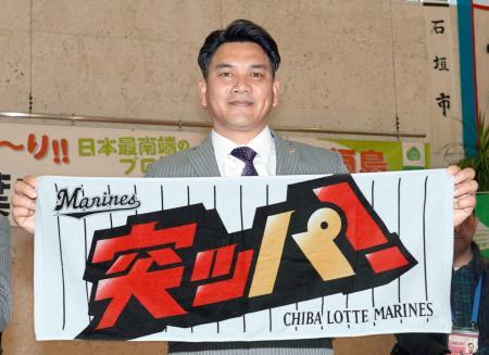 今季のスローガン「突ッパ!」と書かれたタオルを手にするロッテ・井口監督=30日、新石垣空港