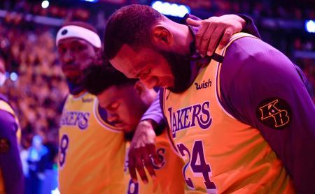 試合前の国歌斉唱で肩を組むレーカーズのジェームズ(右)ら=ロサンゼルス(USA TODAY・ロイター=共同)