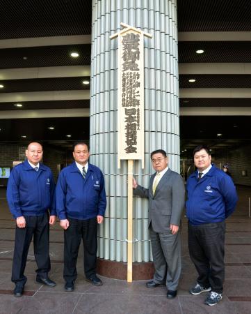 「御免札」の前で写真に納まる大相撲の春場所担当部長の高島親方(右から2人目)ら=10日、エディオンアリーナ大阪