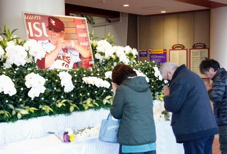 楽天生命パーク宮城に設置された野村克也元監督の献花台に手を合わせる人たち=12日午前、仙台市