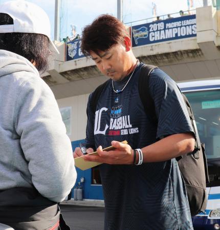 練習を終え、ファンにサインする西武・松坂=日南・南郷