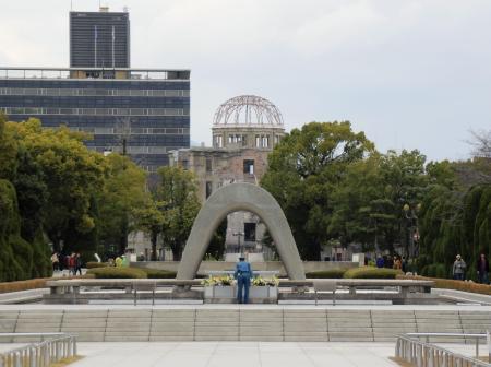 平和記念公園の原爆死没者慰霊碑。奥は原爆ドーム=2018年12月、広島市