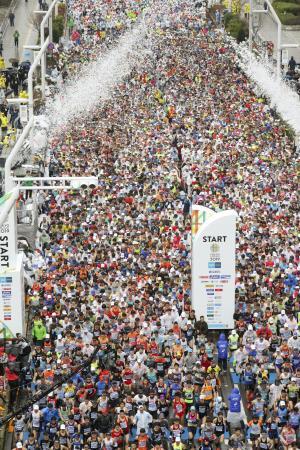 昨年の東京マラソンで、密集して都庁前を一斉にスタートする多くのランナー=東京都新宿区