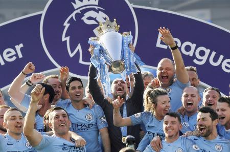 イングランド・プレミアリーグで2連覇を達成し、トロフィーを掲げるマンチェスター・シティーのグアルディオラ監督(中央)=2019年5月(ロイター=共同)