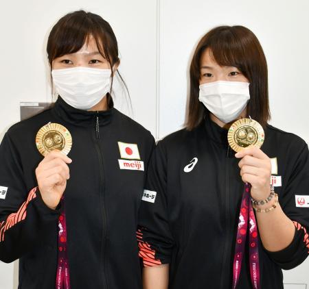 帰国し、金メダルを手に取材に応じるレスリングの川井梨紗子(右)と妹の友香子=23日、成田空港
