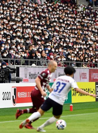 サッカーJ1、横浜FC戦で神戸・イニエスタ(左)らのプレーをマスク姿で観戦する人たち。新型コロナウイルス対策として、歌や肩組みなどの応援行為も禁止された=23日午後、神戸市のノエビアスタジアム神戸