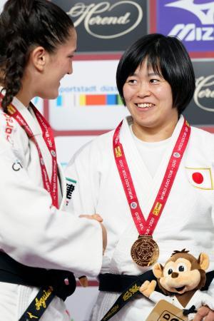 女子78キロ級で優勝し、金メダルを胸に握手を交わす浜田尚里=デュッセルドルフ(共同)