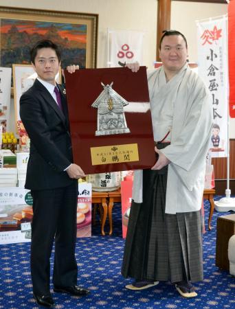 大阪府庁で吉村洋文知事(左)から昨年春場所の優勝盾を受け取り、記念撮影に応じる横綱白鵬=25日