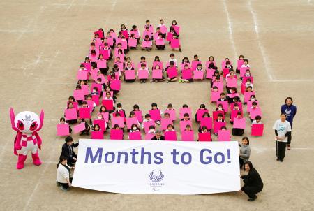 東京パラリンピック開幕まで半年となり、有明西学園の児童たちが描いた「あと6カ月」を表す「6」の人文字=25日午後、東京都江東区